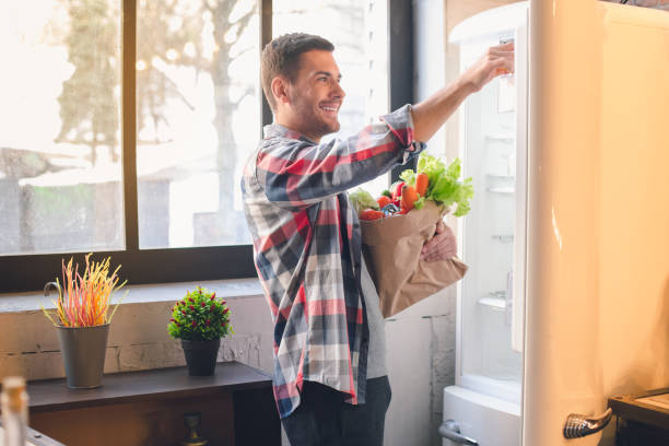 young man vegan with healthy organic food products - happy person buy appliances stock photos and pictures