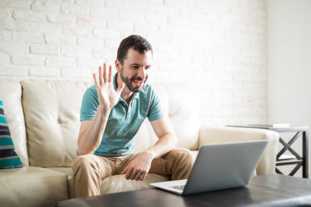 Young man video chatting Good looking Latin man video chatting with his girlfriend and waving his hand to the camera long distance relationship stock pictures, royalty-free photos & images