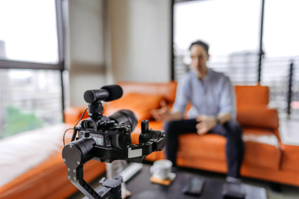 Young man vlogging about his business life Influencer  recording a video with professional camera, focus on foreground presenter stock pictures, royalty-free photos & images