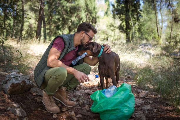Joven voluntario y su perro limpiando el bosque de residuos plásticos y preservando la ecología - foto de stock