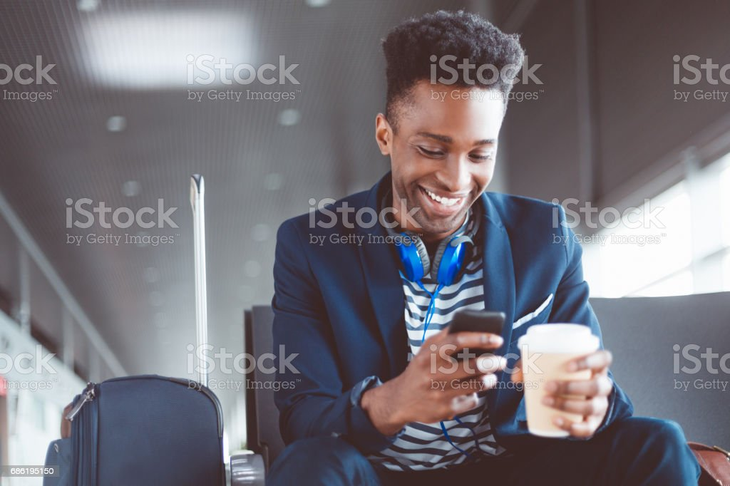 Young man waiting at the airport lounge using mobile phone stock photo