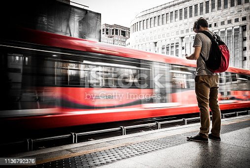 Color image depicting a young man waiting outdoors on a train station platform. The man wears casual khaki trousers and grey t shirt, and a red and black backpack. He is wearing headphones and is looking at his smart phone. In the background a red train speeds past and we can only see it as blurred motion. We can see corporate office building in the distance. Room for copy space.