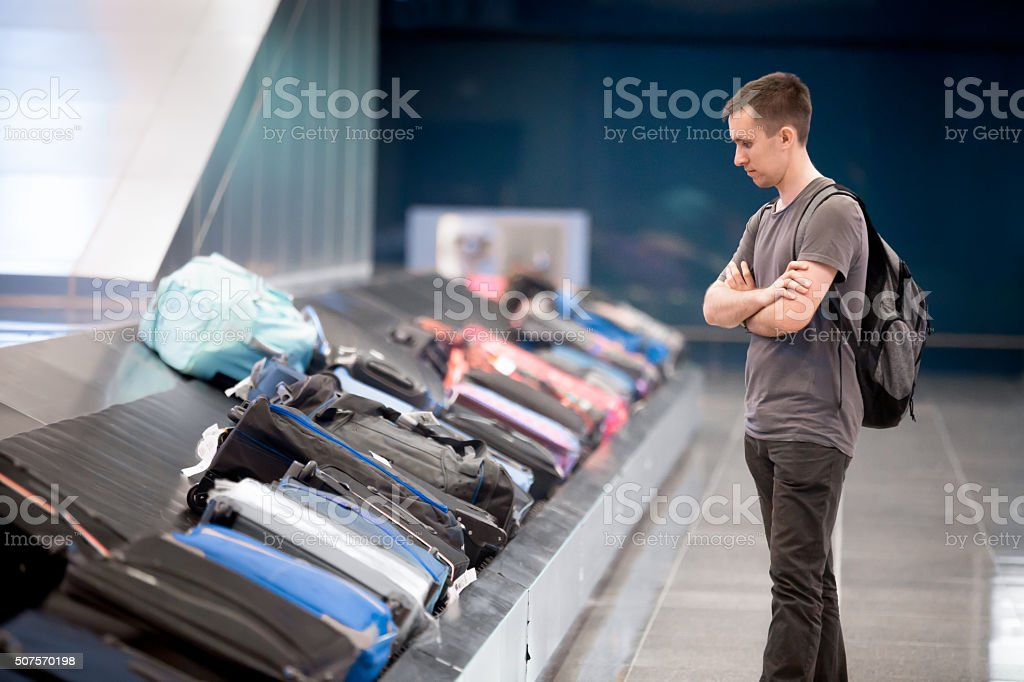Young man waiting for baggage stock photo