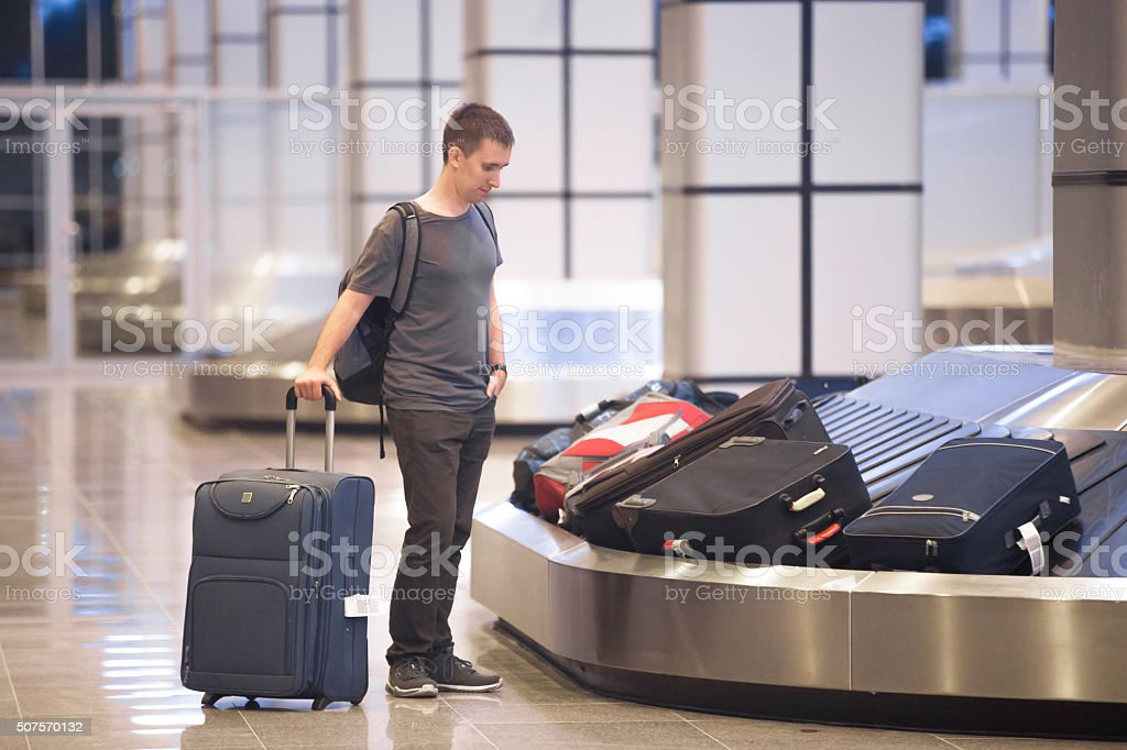 Young man waiting for luggage stock photo