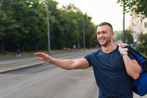 Jonge Man Te Wachten Voor Een Taxi Op Straat Stockfoto en meer beelden van 20-29 jaar