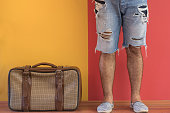 Young man waiting in front of colorful wall with old fashioned suitcase.