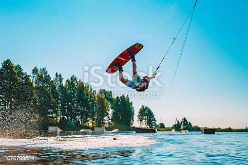 Marupe, Latvia. July 20, 2018. Young man wakeboarding on a lake, making raley, frontroll and jumping the kickers and sliders. Wakeboard.