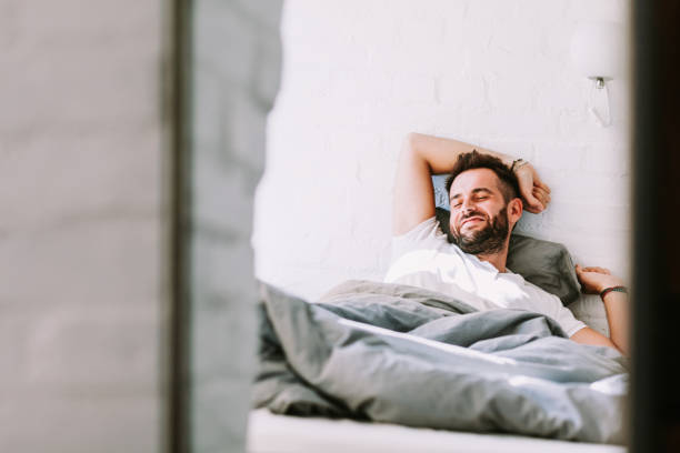 Young man waking up in the bed in the morning stock photo