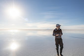 Young man walking and looking away with perfect blue sky reflection in Salar de Uyuni - Uyuni Salt Flats in Bolivia, the incredible mirror-like lake in South America with copy space