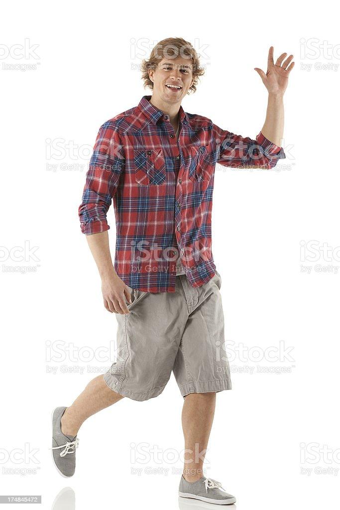 Young man walking and waving hands stock photo