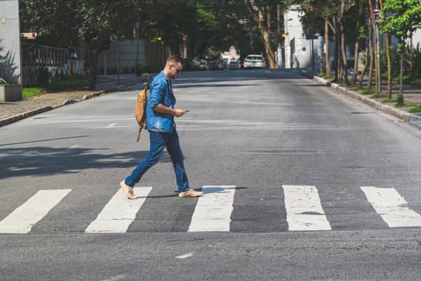 junger mann zu fuß auf einem gehweg auf einer straße in sao paulo - fußgänger stock-fotos und bilder
