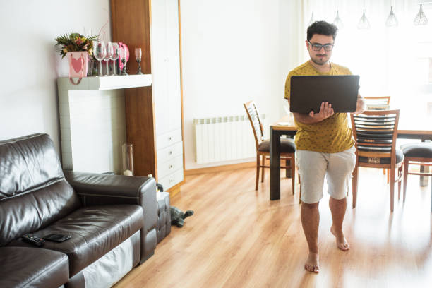 Young man walking at home with his laptop stock photo