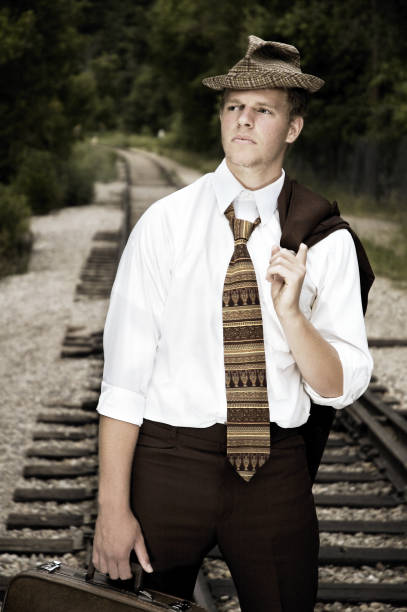 Young Man Walking Down Rail Road Tracks stock photo