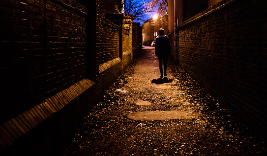 A young man walking home alone at night through a dark alleyway in the UK.