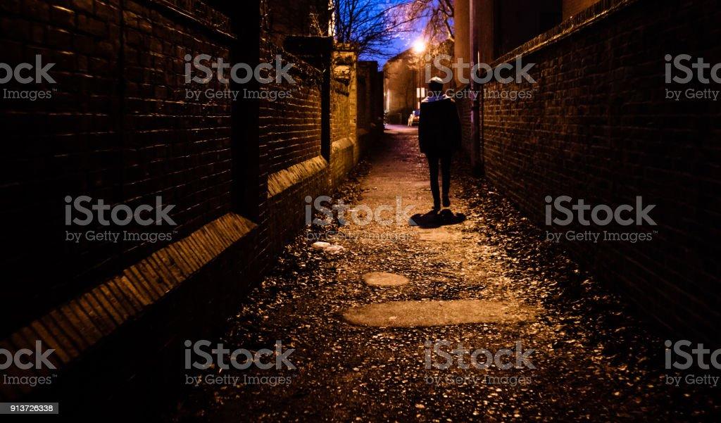 一個年輕人獨自一人在夜裡走在英國的黑暗小巷裡。圖像檔