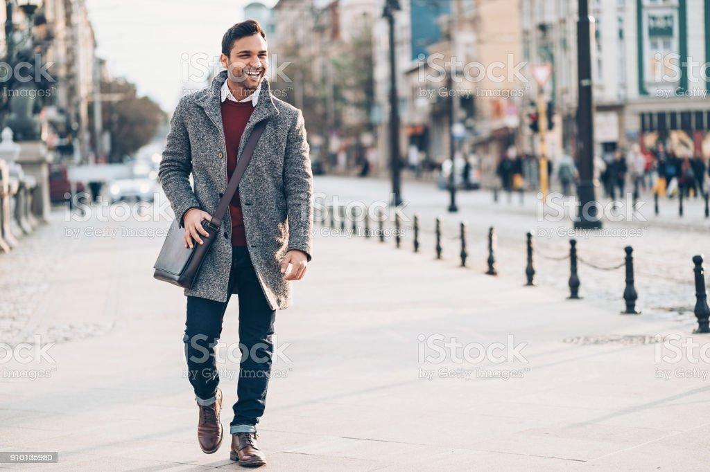 Jovem caminhando na cidade - foto de acervo
