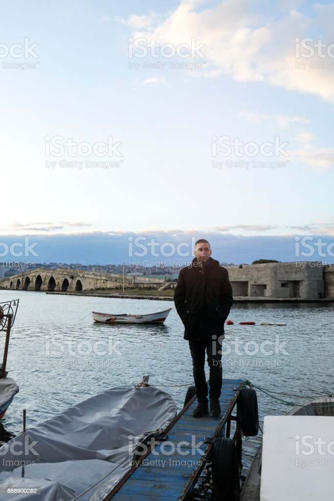Young man walking on pier stock photo