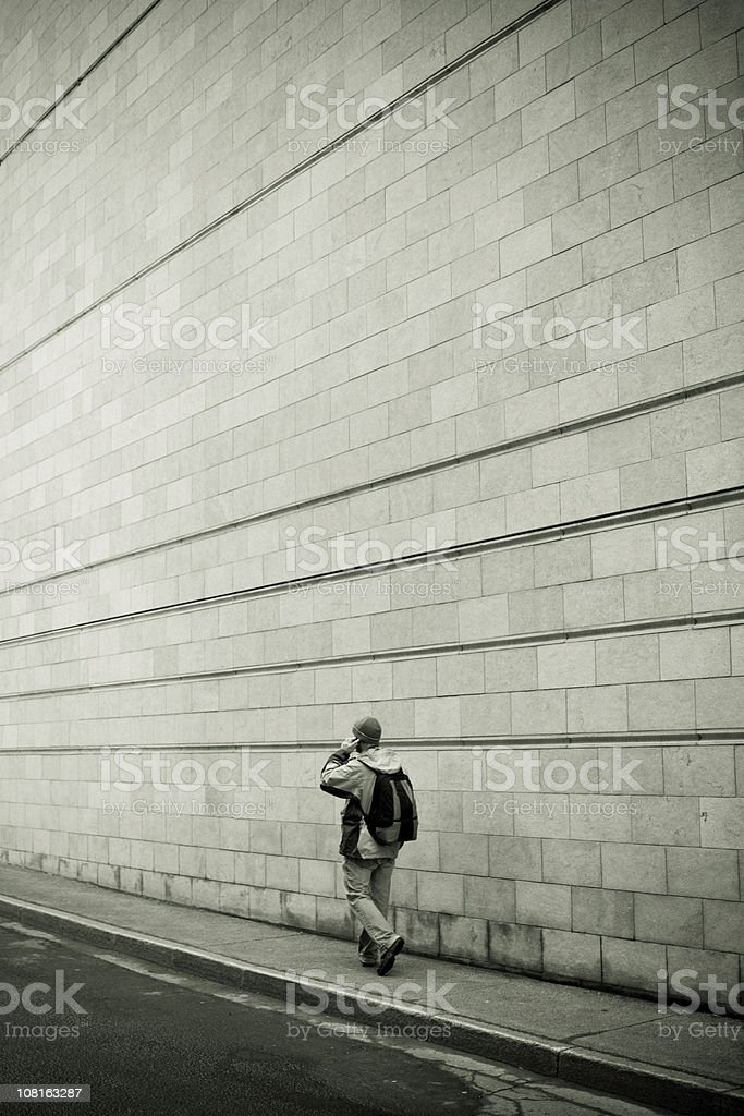 Young Man Walking on Sidewalk Against Concrete Block Wall royalty-free stock photo