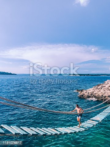 Young Man Walking on Suspension Bridge Over the Sea.