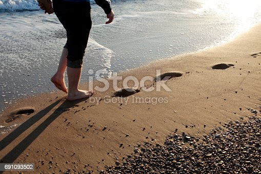174919648 istock photo Young man walking on the beach 691093502