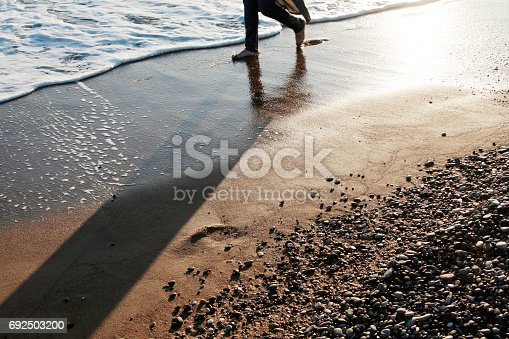 174919648 istock photo Young man walking on the beach 692503200