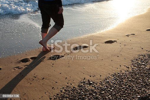 174919648 istock photo Young man walking on the beach 693864106