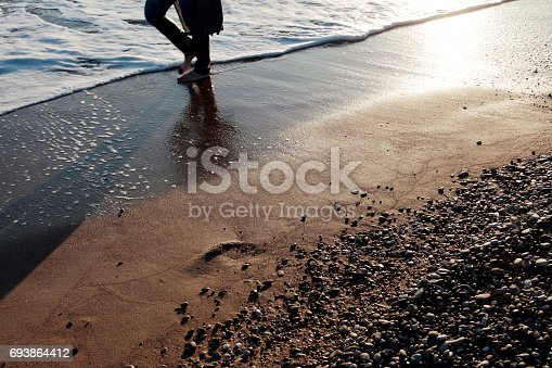 174919648 istock photo Young man walking on the beach 693864412