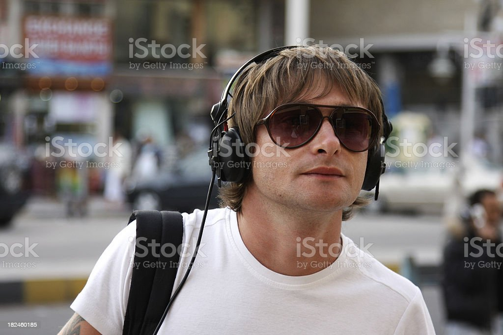 Young man walking on the street and listening music royalty-free stock photo