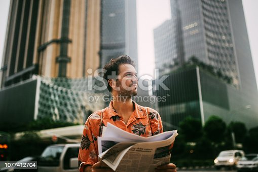 Young man on the streets of Singapore, reading the newspapers. He is wearing casual clothing, enjoying his day in the beautiful Asian city.