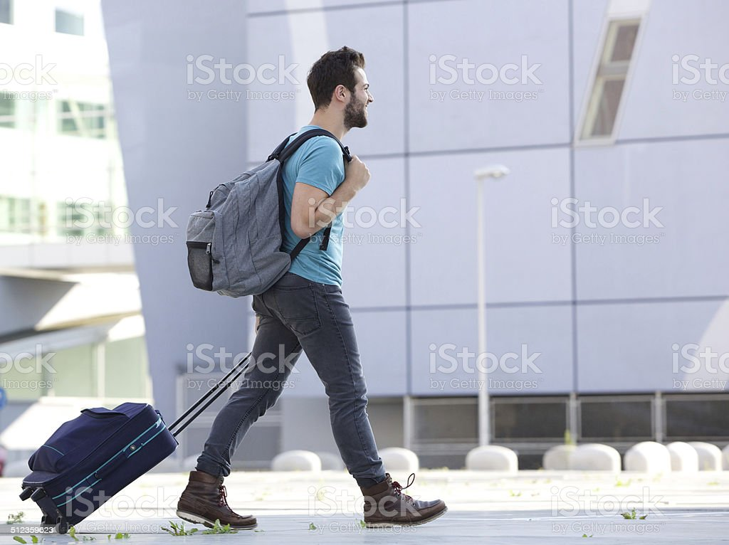 Young man walking outdoors with suitcase royalty-free stock photo