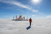 Young man walking to the international flags from different countries in Uyuni salt flat in sunny day with sun rays, Bolivia, South America travel vocation