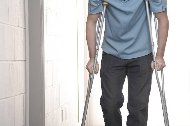 young man walking with crutches - broken leg stock photos and pictures