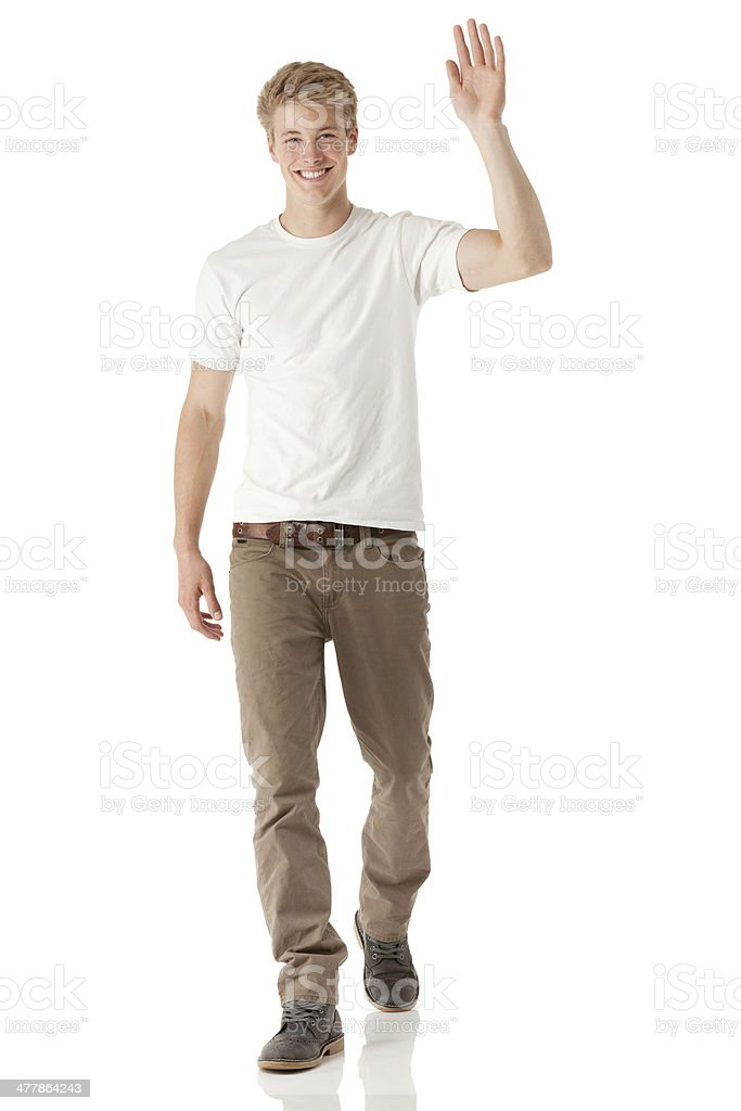 Young man walking with waving hand stock photo