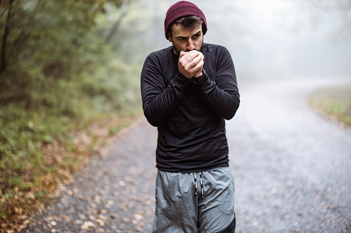 Athletic man blowing into his hands while trying to warm them in nature. Copy space.