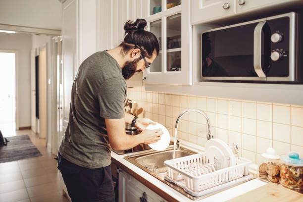 Young man washing dishes at home stock photo