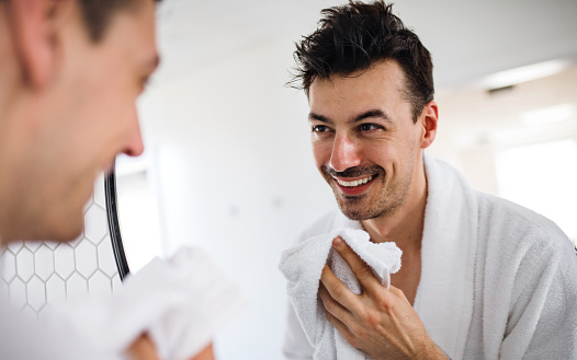 Young Man Washing Face In The Bathroom In The Morning Daily Routine Stock Photo - Download Image Now