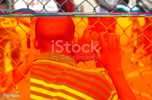 istock Young Man Watching Basketball Game through Fence 172276925