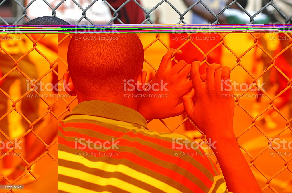 Young Man Watching Basketball Game through Fence stock photo