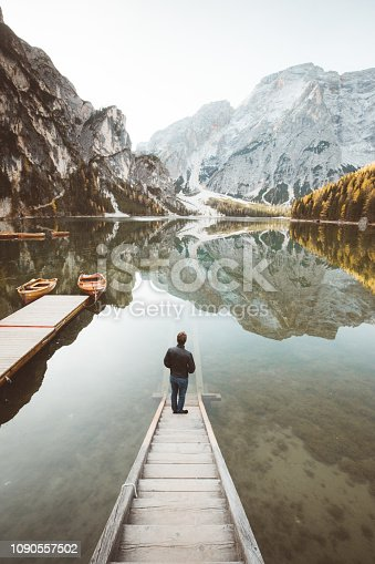 Beautiful view of a young man standing on wooden stairs watching the sunrise at famous Lago di Braies the Dolomites, South Tyrol, Italy
