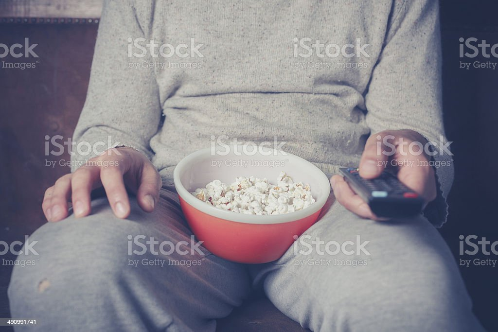 Young man watching television and eating popcorn stock photo