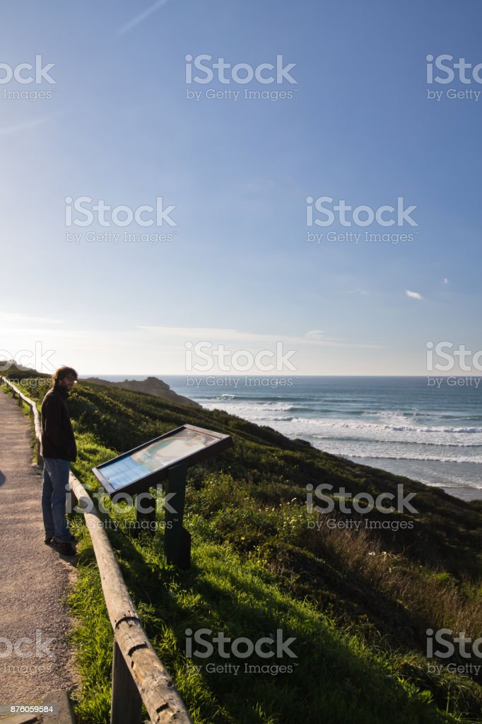 young man watching tourist map on shoreline by arrifana beach, algarve, portugal stock photo