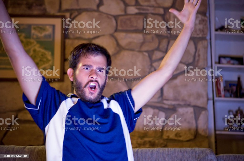 Young man watching tv, raising arms royalty-free stock photo