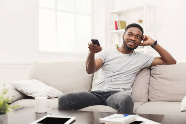 Young man watching tv using remote controller in living room stock photo