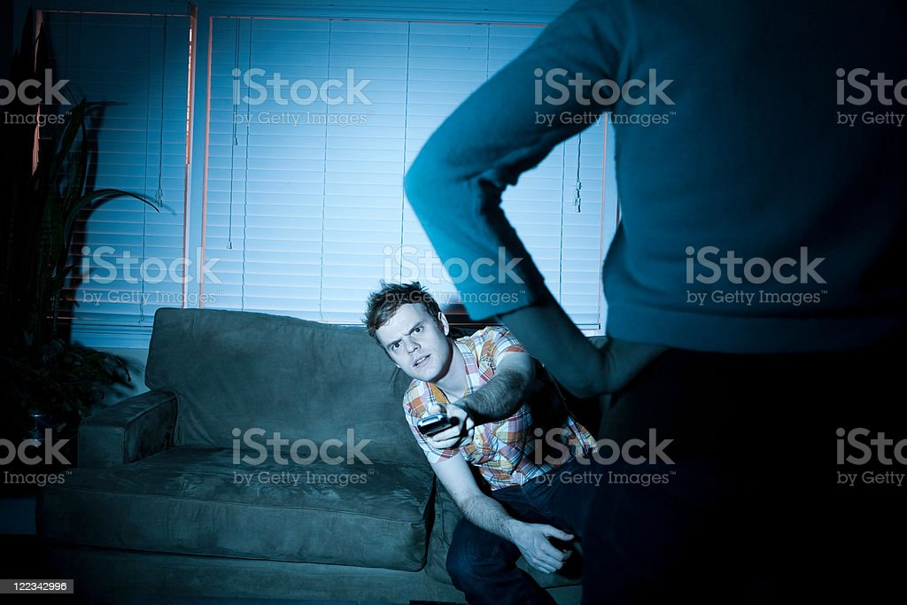 Young man watching tv, woman blocking view stock photo