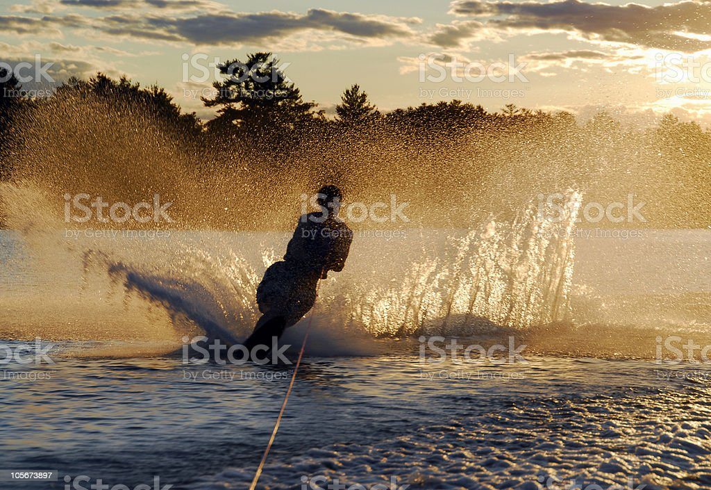 A young man waterskiing at sunset stock photo