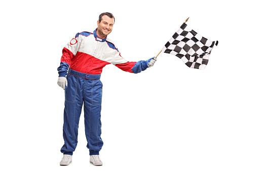 Studio shot of a young male car racer waving a checkered race flag isolated on white background