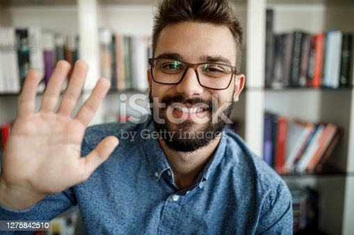 Young man waving with hand on video call at home office