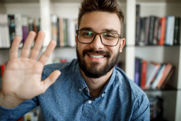 Young man waving with hand on video call at home office stock photo