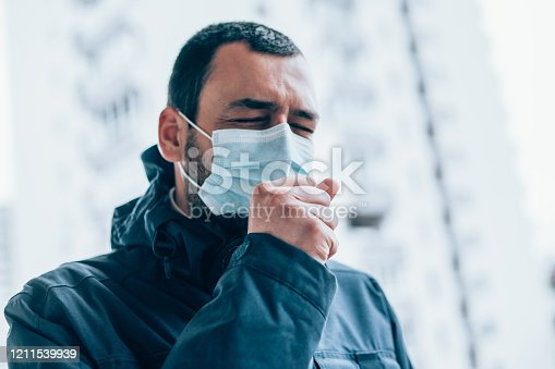 Portrait of young man on the street wearing face protective mask. Young man with closed eyes wear face protective mask and coughing in his arm.