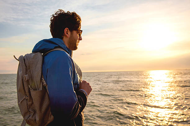 Young man wearing a backpack standing by the sea stock photo